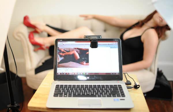 Веб модель позирует перед ноутбуком